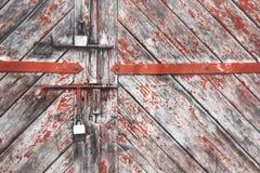 Η πόρτα που κλειδώνεται παλαιά με τα κρεμώντας υποστηρίγματα λουκέτων ανασκοπήσεις που τίθεν&tau Στοκ Φωτογραφίες