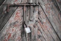 Η πόρτα που κλειδώνεται παλαιά με τα κρεμώντας υποστηρίγματα λουκέτων ανασκοπήσεις που τίθεν&tau Στοκ εικόνα με δικαίωμα ελεύθερης χρήσης