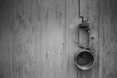 Η πόρτα που κλειδώνεται παλαιά με τα κρεμώντας υποστηρίγματα λουκέτων ανασκοπήσεις που τίθεν&tau Στοκ Φωτογραφία