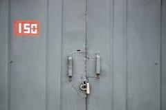 Η πόρτα που κλειδώνεται παλαιά με τα κρεμώντας υποστηρίγματα λουκέτων ανασκοπήσεις που τίθεν&tau Στοκ φωτογραφία με δικαίωμα ελεύθερης χρήσης