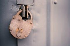 Η πόρτα που κλειδώνεται παλαιά με τα κρεμώντας υποστηρίγματα λουκέτων ανασκοπήσεις που τίθεν&tau Στοκ Εικόνα