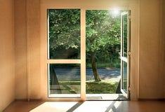 Η πόρτα στο καλοκαίρι Ήλιος-πλημμυρισμένο δωμάτιο με μια ανοιχτή πόρτα στην οδό στοκ εικόνα