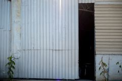 Η πόρτα της αποθήκης εμπορευμάτων που ανοίγει ελαφρώς για να δει το σκοτάδι μέσα για το υπόβαθρο στοκ εικόνες