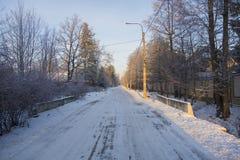 η πόλη κοντά στο δρόμο σιδηροδρόμων λάμπει ήλιος χιονιού στο χειμερινό δάσος Στοκ εικόνα με δικαίωμα ελεύθερης χρήσης
