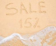 Η πώληση 15% λέξης που γράφεται στην άμμο στην παραλία Στοκ Φωτογραφίες