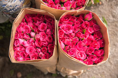 Η πώληση ανθίζει - μια ανθοδέσμη των κόκκινων/ρόδινων τριαντάφυλλων που τυλίγονται στο έγγραφο Στοκ Εικόνα