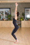 Η πλάγια όψη της γυναίκας που στέκεται με τα χέρια της αύξησε επάνω να προετοιμαστεί για την άσκηση γιόγκας σε μια γυμναστική στοκ εικόνα