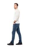 Η πλάγια όψη του νέου χαλαρωμένου περιστασιακού ατόμου που περπατά με παραδίδει τις τσέπες ανατρέχοντας Στοκ Εικόνες