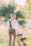 Η πλάτη του νεόνυμφου στα γκρίζα εσώρουχα, το άσπρο πουκάμισο και μαύρα suspenders που φέρνουν το ποδήλατο στο υπόβαθρο Στοκ φωτογραφία με δικαίωμα ελεύθερης χρήσης