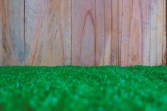 Η πλαστική τεχνητή πράσινη χλόη με τον ξύλινο τοίχο Στοκ φωτογραφία με δικαίωμα ελεύθερης χρήσης