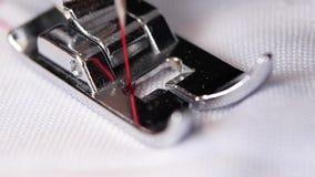 Η ράβοντας βελόνα με το κόκκινο νήμα κάνει τις βελονιές σε σε αργή κίνηση απόθεμα βίντεο