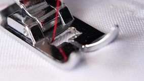 Η ράβοντας μηχανή κάνει ένα κόκκινο νήμα να ράψει σε σε αργή κίνηση φιλμ μικρού μήκους