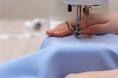 Η ράβοντας μηχανή κινηματογραφήσεων σε πρώτο πλάνο, βελόνα ράβει Το χέρι seamstress κοριτσιών κρατά το ύφασμα στοκ εικόνα με δικαίωμα ελεύθερης χρήσης