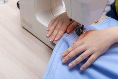 Η ράβοντας μηχανή κινηματογραφήσεων σε πρώτο πλάνο, βελόνα ράβει Το χέρι seamstress κοριτσιών κρατά το ύφασμα στοκ φωτογραφία με δικαίωμα ελεύθερης χρήσης