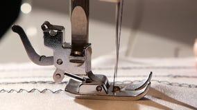 Η ράβοντας μηχανή ράβει μια βελονιά τρεκλίσματος στο άσπρο ύφασμα κίνηση αργή φιλμ μικρού μήκους