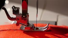 Η ράβοντας μηχανή ράβει μια βελονιά τρεκλίσματος στο κόκκινο ύφασμα κίνηση αργή απόθεμα βίντεο
