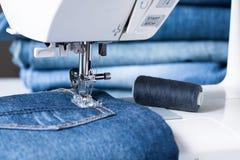 Η ράβοντας μηχανή ράβει το ύφασμα τζιν Στοκ Εικόνα