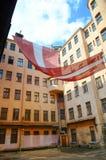 Η Ρήγα, Λετονία - 10 Αυγούστου 2014 - τεράστια λετονική εθνική σημαία κρεμά στην προηγούμενη έδρα KGB στη Ρήγα (το σπίτι γωνιών), Στοκ Εικόνα