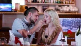Η ρομαντική ατμόσφαιρα στο εστιατόριο, το νέους άνδρα εραστών και τη γυναίκα σε έναν καφέ κατά μια ρομαντική ημερομηνία, τα μάτια απόθεμα βίντεο