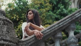 Η ρομαντική γυναίκα στέκεται κοντά στα κιγκλιδώματα πετρών σε έναν κήπο στην ημέρα απόθεμα βίντεο