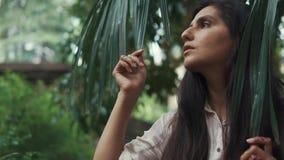Η ρομαντική γυναίκα brunette στέκεται σε έναν κήπο κάτω από το δέντρο με τα μεγάλα φύλλα απόθεμα βίντεο
