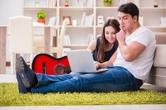 Η ρομαντική κιθάρα παιχνιδιού ζευγαριού στο πάτωμα Στοκ Φωτογραφία