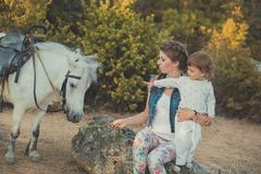 Η ρομαντική όμορφη γυναικεία νέα μητέρα σκηνής με τη χαριτωμένη κόρη μωρών της απολαμβάνει το χρόνο μαζί στη σίτιση περπατήματος  Στοκ φωτογραφία με δικαίωμα ελεύθερης χρήσης