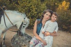 Η ρομαντική όμορφη γυναικεία νέα μητέρα σκηνής με τη χαριτωμένη κόρη μωρών της απολαμβάνει το χρόνο μαζί στη σίτιση περπατήματος  Στοκ εικόνες με δικαίωμα ελεύθερης χρήσης