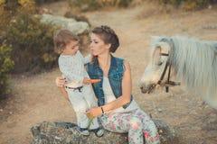 Η ρομαντική όμορφη γυναικεία νέα μητέρα σκηνής με τη χαριτωμένη κόρη μωρών της απολαμβάνει το χρόνο μαζί στη σίτιση περπατήματος  Στοκ Εικόνες