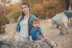 Η ρομαντική όμορφη γυναικεία νέα μητέρα σκηνής με τη χαριτωμένη κόρη μωρών της απολαμβάνει το χρόνο μαζί στη σίτιση περπατήματος  Στοκ εικόνα με δικαίωμα ελεύθερης χρήσης