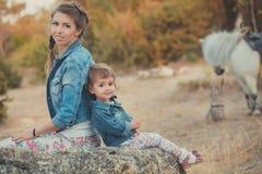 Η ρομαντική όμορφη γυναικεία νέα μητέρα σκηνής με τη χαριτωμένη κόρη μωρών της απολαμβάνει το χρόνο μαζί στη σίτιση περπατήματος  Στοκ Φωτογραφίες