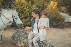 Η ρομαντική όμορφη γυναικεία νέα μητέρα σκηνής με τη χαριτωμένη κόρη μωρών της απολαμβάνει το χρόνο μαζί στη σίτιση περπατήματος  Στοκ Εικόνα