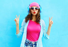 Η δροσερή γυναίκα μόδας αρκετά ακούει τη μουσική στα ακουστικά πέρα από το ζωηρόχρωμο μπλε Στοκ Εικόνες