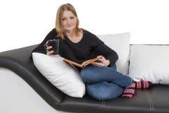 Η δροσερή νέα γυναίκα διαβάζει ένα βιβλίο στον καναπέ Στοκ Εικόνες