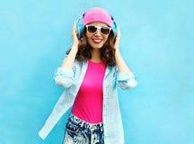 Η δροσερή χαμογελώντας γυναίκα μόδας αρκετά ακούει τη μουσική στα ακουστικά πέρα από το ζωηρόχρωμο μπλε Στοκ εικόνες με δικαίωμα ελεύθερης χρήσης