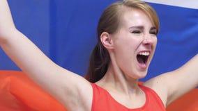 Η ρωσική νέα γυναίκα γιορτάζει το κράτημα της σημαίας της Ρωσίας σε σε αργή κίνηση φιλμ μικρού μήκους
