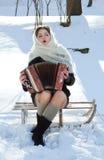 Η ρωσική ομορφιά σε ένα άσπρο πλεκτό μαντίλι στο χιόνι παίζει το χειμώνα ακκορντέον Στοκ Φωτογραφία
