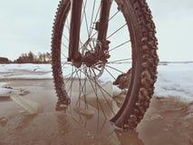 Η ρόδα ποδηλάτων βουνών έσπασε μέσω του πάγου στο νερό Απολαύστε χειμερινό με τη διασκέδαση Στοκ Φωτογραφία
