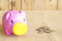 Η ρόδινα piggy τράπεζα και το υπόβαθρο νομισμάτων είναι ξύλινες Στοκ εικόνες με δικαίωμα ελεύθερης χρήσης