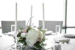Η ρύθμιση γαμήλιων πινάκων είναι διακοσμημένη με τα φρέσκα λουλούδια και τα άσπρα κεριά Γάμος floristry Ανθοδέσμη με τα τριαντάφυ στοκ εικόνες
