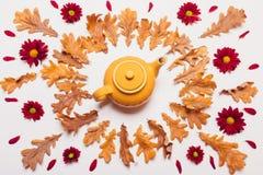 Η ρύθμιση κίτρινο teapot, ξεραίνει τα φύλλα και το κόκκινο πνεύμα λουλουδιών Στοκ φωτογραφίες με δικαίωμα ελεύθερης χρήσης