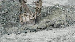 Η σέσουλα του εκσκαφέα σκάβει την τρύπα Ο εκσκαφέας σκάβει το κοίλωμα στο έδαφος για την κατασκευή ή τη μεταλλεία Μεταλλεία και ε απόθεμα βίντεο