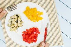 Η σαλάτα από τα φυσικά λαχανικά στο άσπρο πιάτο για το πρόγευμα τεμάχισε τα φρέσκες γλυκά πιπέρια και τη μελιτζάνα στο χαλί μπαμπ Στοκ Φωτογραφίες