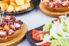 Η σαλάτα και το ξύλινο πιάτο του της Γαλικίας ύφους μαγείρεψαν το χταπόδι με τις πατάτες, το ελαιόλαδο πάπρικας και gallega pulpo Στοκ φωτογραφία με δικαίωμα ελεύθερης χρήσης