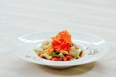 Η σαλάτα με το πιπέρι της Τουρκίας ξεφυτρώνει, cornichons και λαχανικά, σε ένα άσπρο πιάτο σε ένα ελαφρύ υπόβαθρο Στοκ Εικόνες