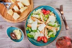 Η σαλάτα με το στήθος κοτόπουλου, τυρί παρμεζάνας, croutons, ντομάτες, ανάμιξε τα πράσινα, το μαρούλι και το ποτήρι του κρασιού σ Στοκ Εικόνα
