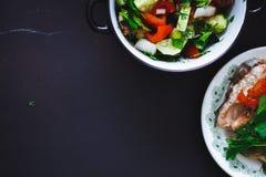 Η σαλάτα φρέσκων λαχανικών στο πιάτο και τα ψάρια στο μαύρο υπόβαθρο, κλείνουν επάνω, τοπ άποψη τρόφιμα υγιή διάστημα αντιγράφων στοκ εικόνα
