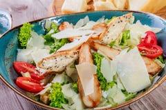 Η σαλάτα με το στήθος κοτόπουλου, τυρί παρμεζάνας, croutons, ντομάτες, ανάμιξε τα πράσινα, το μαρούλι και το ποτήρι του κρασιού στοκ εικόνες