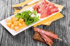 Η σαλάτα Arugula, prosciutto, μοτσαρελών και πεπονιών, κλείνει επάνω Στοκ εικόνα με δικαίωμα ελεύθερης χρήσης