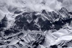 Η σειρά βουνών το χειμώνα στη θύελλα χιονιού: οι υψηλές αιχμές καλύπτονται με το χιόνι και ο πάγος κατεβαίνει τις κλίσεις, όλες λ Στοκ φωτογραφία με δικαίωμα ελεύθερης χρήσης